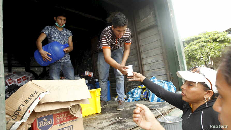 Volunteers offer food and water to people in Pedernales, after an earthquake struck off Ecuador's Pacific coast, April 21, 2016.