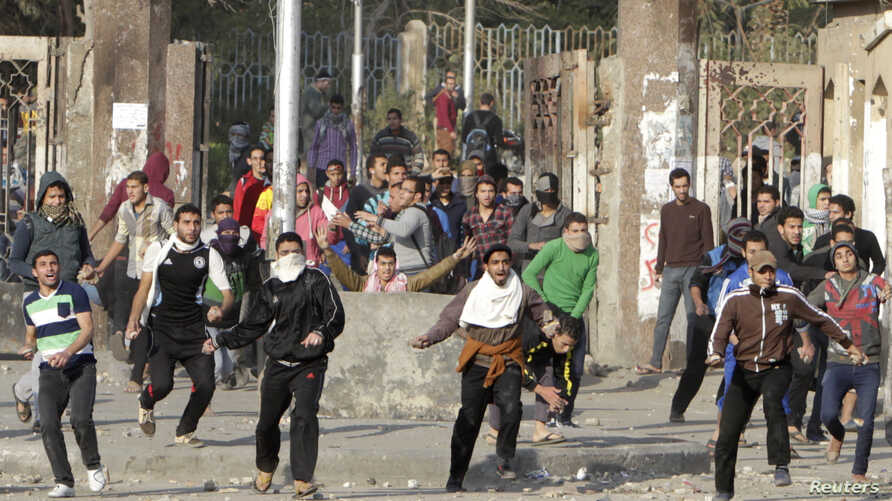 Students of Al-Azhar University, who are supporters of the Muslim Brotherhood and deposed Egyptian President Mohamed Morsi, clash with riot police and residents in Cairo's Nasr City, Jan. 8, 2014.