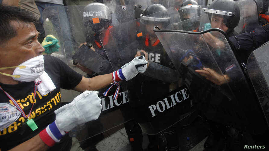 An anti-government protester fights with the police at the barricade near the Finance Ministry buildings in Bangkok, Nov. 25, 2013. (Reuters)