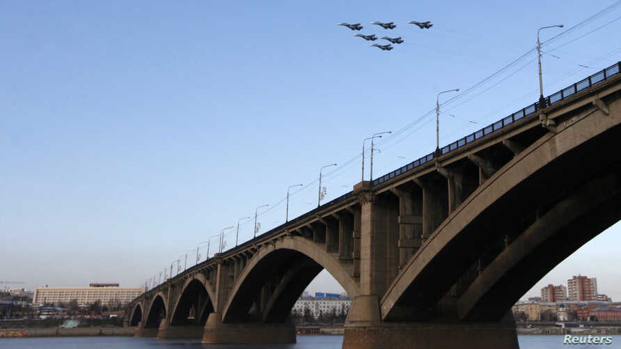 """FILE - Jet fighters from the Su-30 SM """"Sokoly Rossii"""" (Falcons of Russia) aerobatic team fly during rehearsals for a show above the Yenisei River in Krasnoyarsk, Siberia, October 2014."""