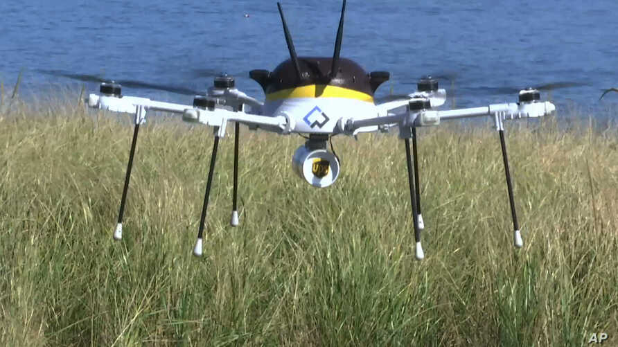 A still image taken from video shows a test drone making a UPS delivery lands on Children's Island in Marblehead, Mass., Sept. 22, 2016.