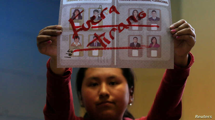 "A member of the electoral committee shows a ballot that reads ""Out, tyrant"" during the counting of votes in the nationwide judicial elections in La Paz, Bolivia, Dec. 3, 2017."
