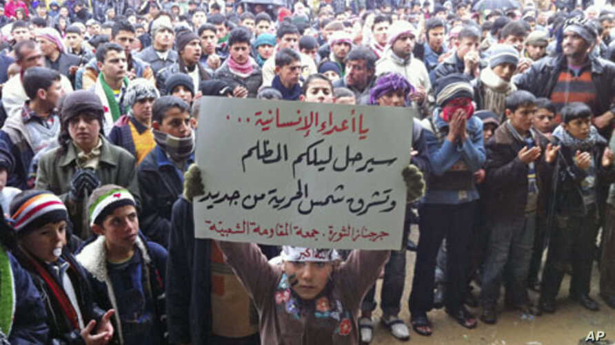 Demonstrators take part in a protest against Syria's President Bashar al-Assad - carrying a sign that reads, 'Enemies of humanity your dark night will go and the new dawn of freedom will rise' - in Jerjenaz, near Idlib, February 17, 2012.