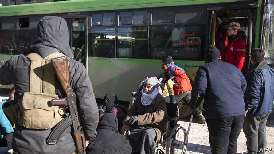 Syrians gather during an evacuation operation of rebel fighters and their families  from rebel-held neighborhoods on Dec. 15, 2016 in the embattled city of Aleppo.