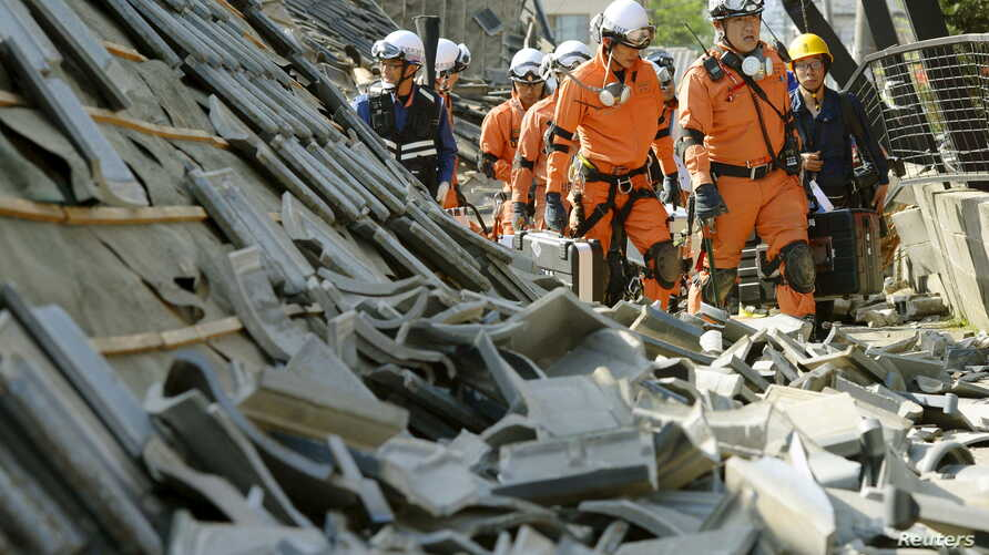 Firefighters walk among collapsed houses caused by an earthquake in Mashiki town, Kumamoto prefecture, southern Japan, in this photo taken by Kyodo, April 15, 2016.