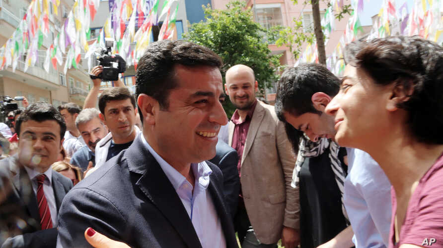 Greeted by supporters, Selahattin Demirtas, leader of pro-Kurdish Peoples' Democracy Party, smiles as he arrives at his party headquarters in Ankara, Turkey,  June 9, 2015.