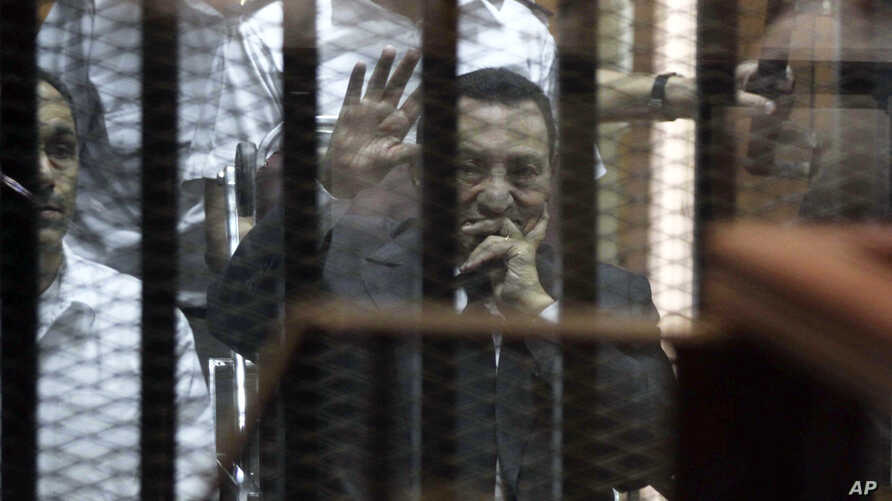 Ousted Egyptian President Hosni Mubarak, sitting in a defendants cage, waves during a court hearing as his son Gamal, left, in Cairo, Egypt, Wednesday, May 21, 2014. An Egyptian court has convicted Mubarak of embezzlement and sentenced him to three y