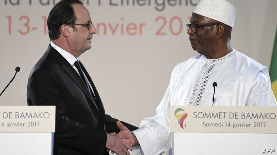 French President Francois Hollande, left, and Malian President Ibrahim Boubacar Keita shake hands during a joint news conference following the Africa-France summit in Bamako, Jan. 14, 2017. Both called on Yahya Jammeh to step down in Gambia when his