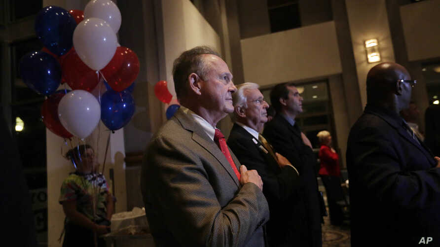 Former Alabama Chief Justice and U.S. Senate candidate Roy Moore, stops to say the Pledge of Allegiance as he walks around greeting supporters before his election party, Tuesday, Sept. 26, 2017, in Montgomery, Alabama.