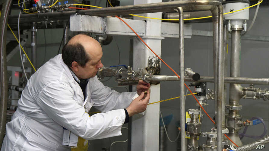 FILE - An unidentified International Atomic Energy Agency (IAEA) inspector cuts the connections between the twin cascades for 20 percent uranium enrichment at the Natanz facility, some 200 miles (322 kilometers) south of the capital Tehran, Iran.