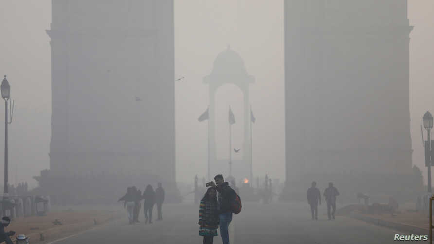 FILE - People take a selfie in front of the India Gate war memorial on a smoggy winter morning in New Delhi, India, Dec. 26, 2017.