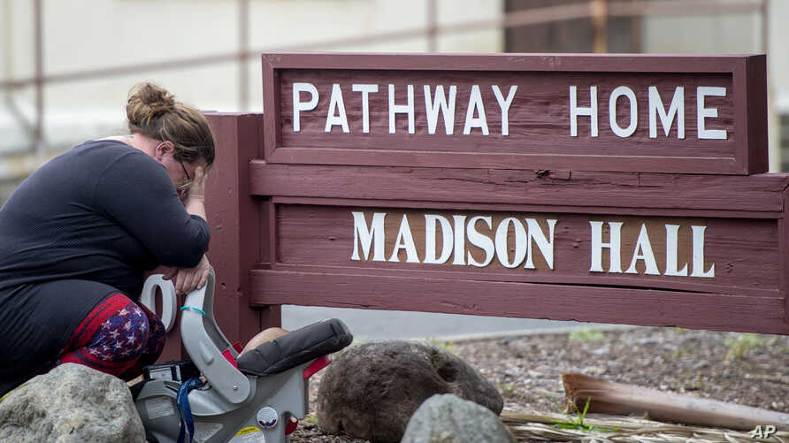 A woman cries after placing flowers at a sign at the Veterans Home of California, the morning after a hostage situation in Yountville, Calif., March 10, 2018.  A daylong siege at The Pathway Home ended Friday evening with the discovery of four bodies