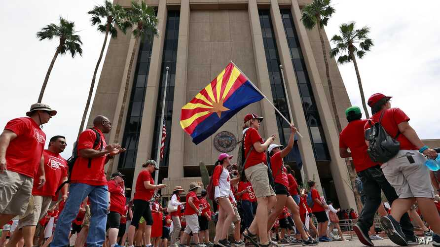 Teachers rally outside of Arizona Gov. Doug Ducey's Executive Tower in Phoenix on their third day of walkouts, April 30, 2018.