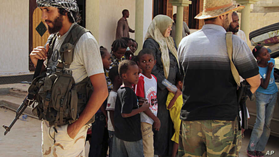 Children and families are seen stranded outside a mosque guarded by revolutionary fighters in Sirte, Libya. After NATO's heavy bombing on Sunday, hundreds of families are leaving the city. Some remain stranded on the outskirts due to lack of transpor