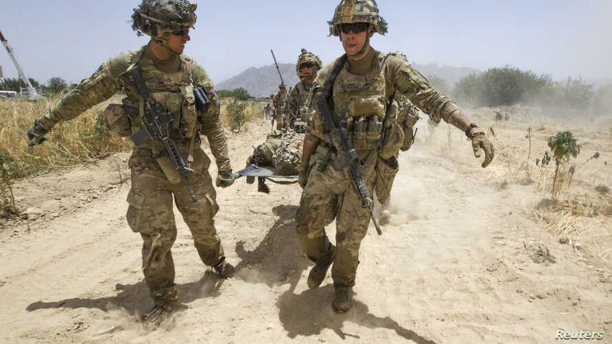 U.S. Army soldiers carry Sgt. Matt Krumwiede, who was wounded by an improvised explosive device (IED), towards a Blackhawk Medevac helicopter in southern Afghanistan June 12, 2012.