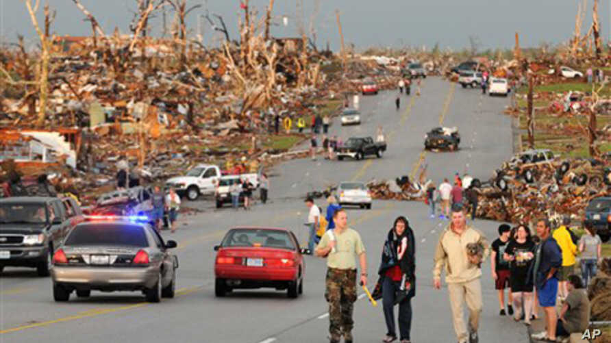 Residents of Joplin, Mo, walk west on 26th Street near Maiden Lane after a tornado hit the southwest Missouri city on Sunday evening, May 22, 2011. The tornado tore a path a mile wide and four miles long destroying homes and businesses. (AP Photo/Mik