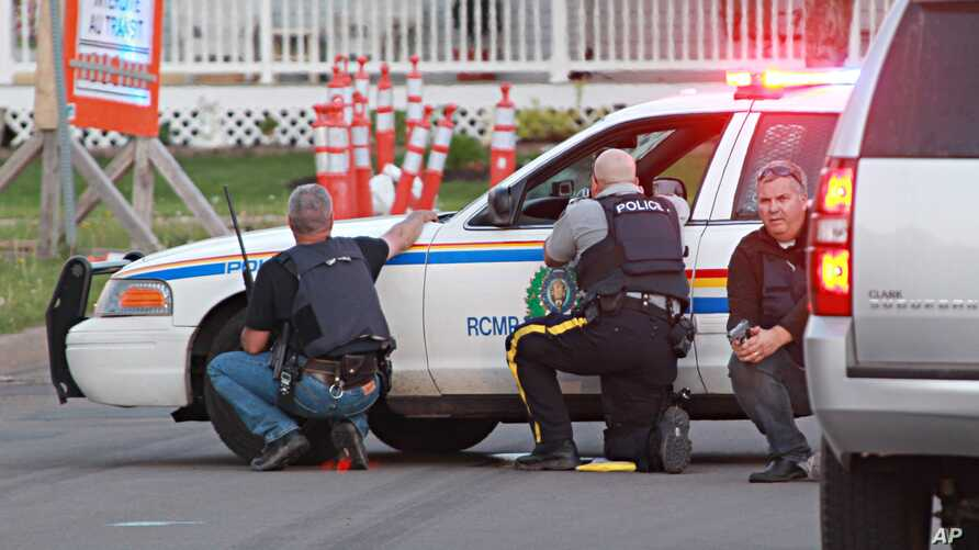 Police officers take cover behind their vehicles in Moncton, New Brunswick, June 4, 2014.