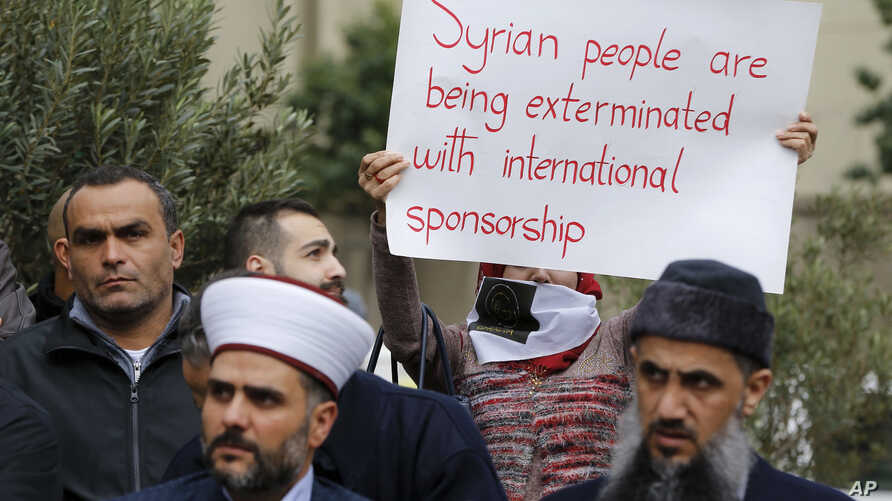 A woman holds a placard during a protest in solidarity with residents of the Syrian capital's eastern suburb of Ghouta, in front the Russian embassy in Beirut, Lebanon, Sunday, Feb. 25, 2018.