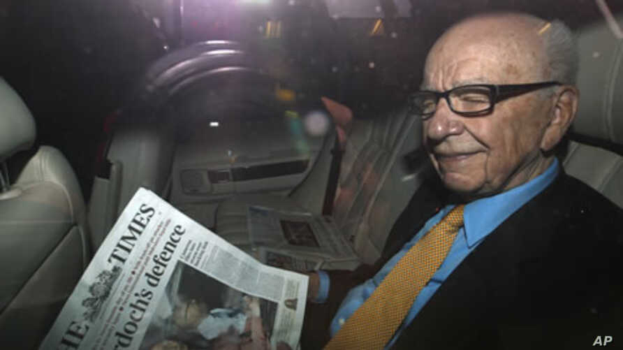 News Corp Chief Executive and Chairman Rupert Murdoch holds a copy of The Times newspaper as he leaves his home in London July 20, 2011