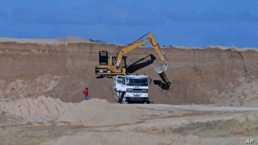 A excavator dumps bauxite ore into a dump truck at a mine belonging to China's Bosai Minerals Group in Linden, (File)