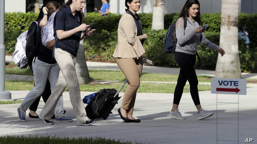 """Students walk past a """"Vote"""" sign next to an early voting site on the Florida International University campus, Oct. 23, 2018, in Miami."""