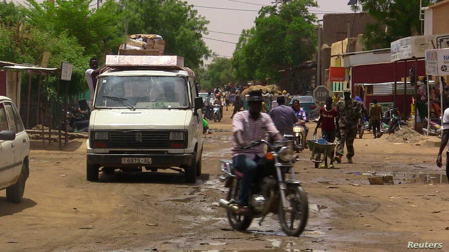 FILE - A man rides a motorcycle down a street in the northern city of Gao, Mali, July 22, 2016.