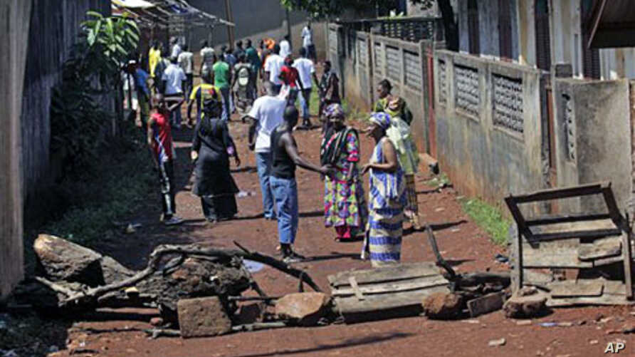 Residents of the mostly Peul suburb of Bambeto, Conakry, walk back to their homes behind barricades they set after a shooting incident, 17 Nov 2010