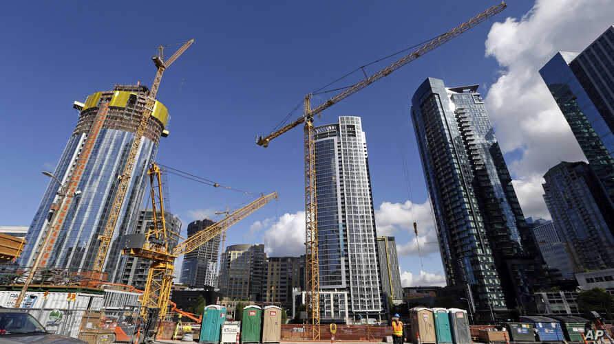 FILE - In this  Oct. 11, 2017 file photo, construction cranes fill a block across from an Amazon building in Seattle.