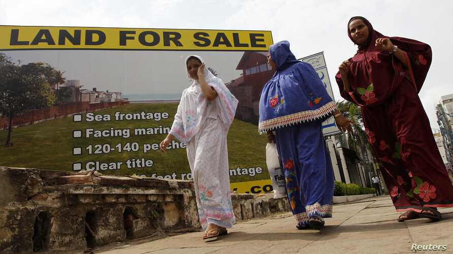 Three women walk past a sign advertising land for sale in Colombo, Sept. 14, 2010.
