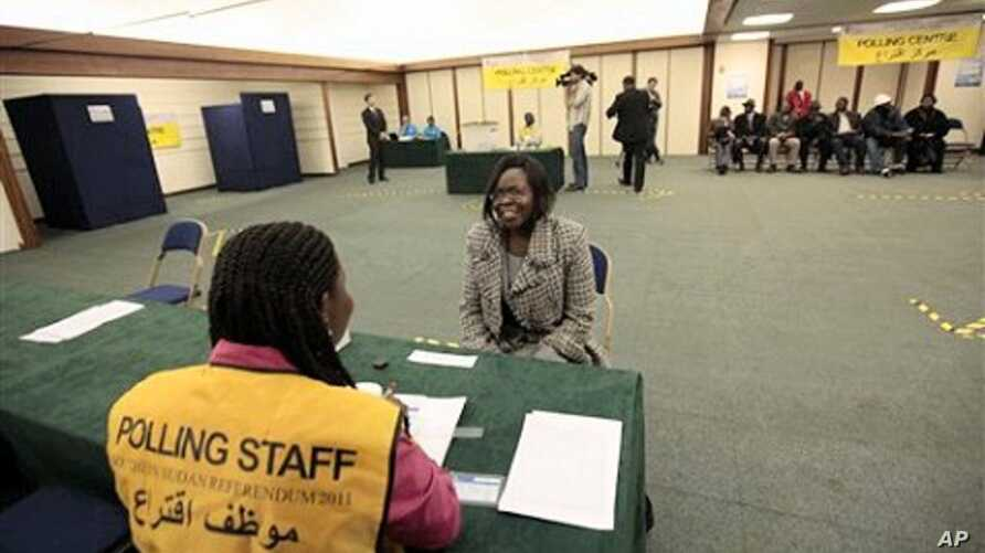 A Southern Sudanese woman smiles as she has her identification documents checked by an official before casting her vote for the Southern Sudan Referendum in a special polling station set up in central London, 09 Jan 2011.