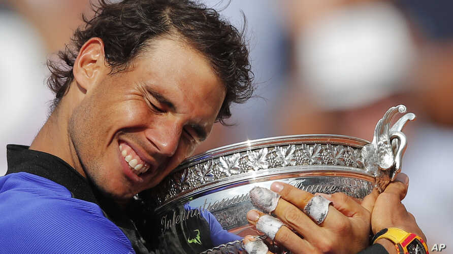 Spain's Rafael Nadal holds the trophy as he celebrates winning his tenth French Open title against Switzerland's Stan Wawrinka in three sets, during their men's final match of the French Open tennis tournament at the Roland Garros stadium, in Paris,