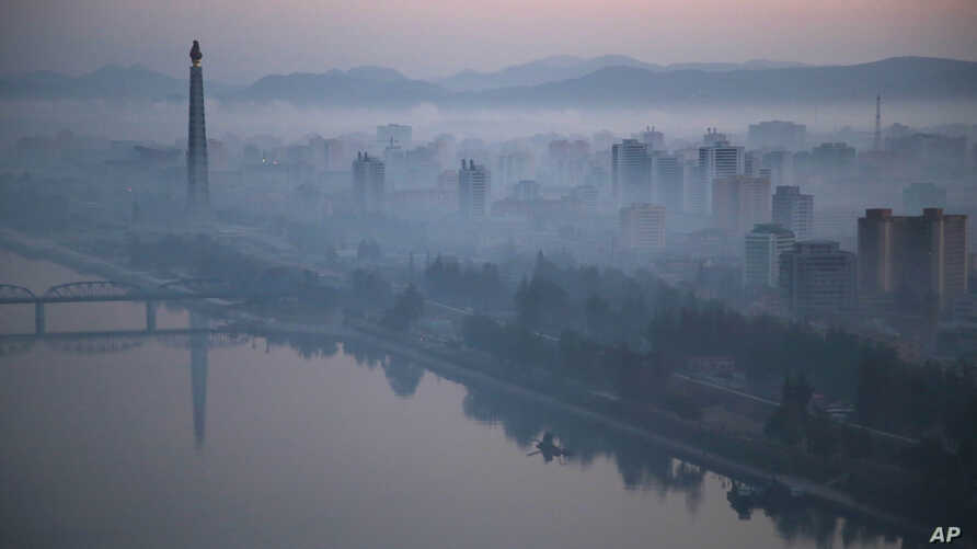 Dawn breaks over Pyongyang, North Korea, as buildings poke through the midst and the Juche Tower, left, stands by the Taedong riverbank on Tuesday, Oct. 13, 2015.