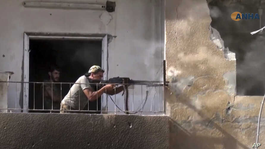 FILE - This frame grab from video released Aug. 3, 2017, and provided by Hawar News Agency, a Syrian Kurdish activist-run media group, shows a fighter from the U.S.-backed Syrian Democratic Forces firing his weapon during clashes with Islamic State g