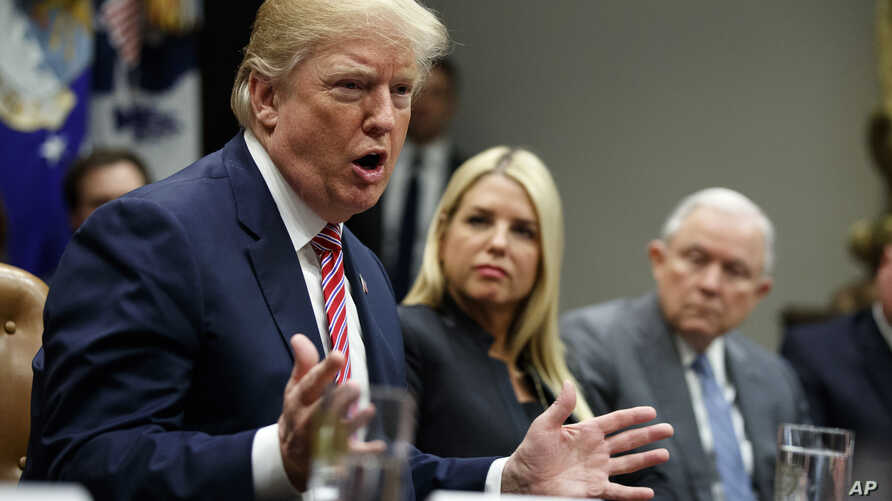 Florida Attorney General Pam Bondi, center, and Attorney General Jeff Sessions, right, watch as President Donald Trump speaks during a meeting with state and local officials to discuss school safety, in the Roosevelt Room of the White House, Feb. 22,