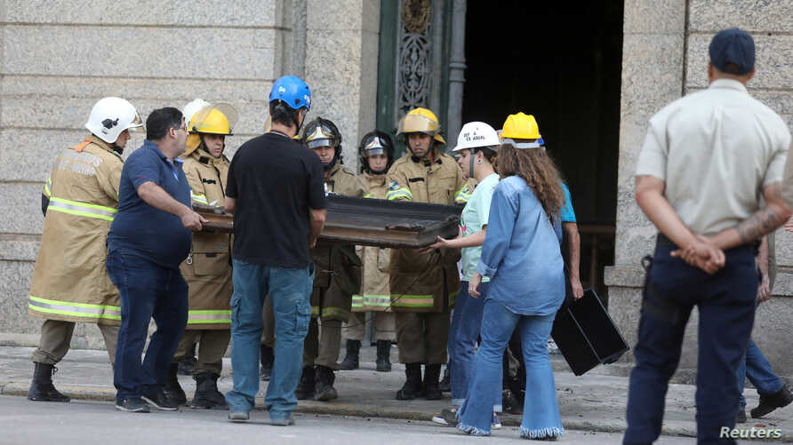 Rescue workers and museum staff carry a picture at the National Museum of Brazil in Rio de Janeiro, Brazil, Sept. 3, 2018.