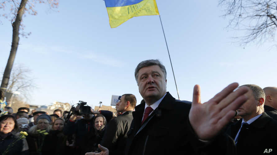 """FILE - Ukraine's President Petro Poroshenko speaks with people after a wreath laying ceremony at the monument to the fallen Heroes of the """"Heavenly Sotnya (Hundred),"""" in Kyiv, Ukraine, Nov. 21, 2014."""