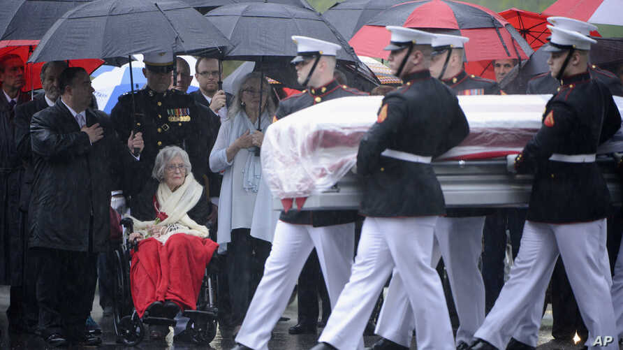 In this U.S. Army photo by Rachel Larue/Arlington National Cemetery, Annie Glenn, seated, widow of John Glenn, watches as members of the U.S. Marine Corps from Marine Barracks Washington carry the casket of her husband during his graveside service at