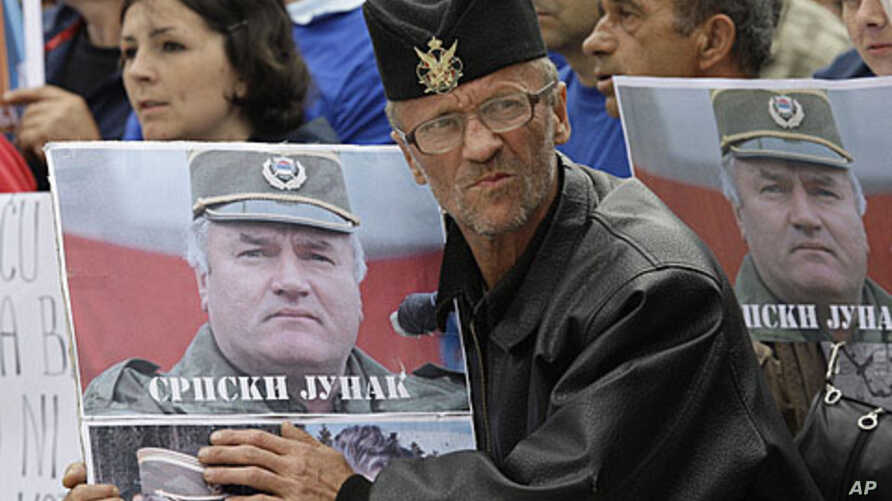 A Bosnian Serb man holds a photo of former General Ratko Mladic during a protest in Kalinovik, Bosnia, hometown of the Bosnian Serb wartime military leader, May 29, 2011