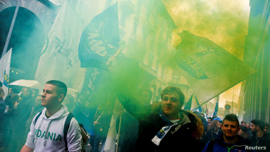 Italian Northern League supporters hold flares as they arrive at political rally led by leader Matteo Salvini, in Milan, Italy, Feb. 24, 2018.