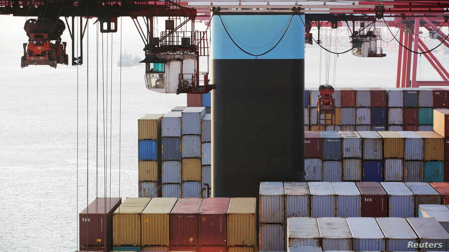FILE - Containers are seen unloaded from the Maersk's Triple-E giant container ship Maersk Majestic, one of the world's largest container ships, at the Yangshan Deep Water Port, part of the  Shanghai Free Trade Zone, in Shanghai, China, Sept. 24, 201...