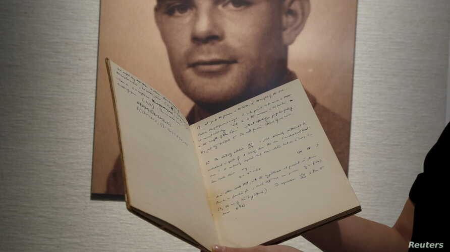 FILE - A notebook of British computer science pioneer Alan Turing is displayed in front of a photo of him during an auction preview in Hong Kong, March 19, 2015. The head of Britain's digital spy agency has paid tribute to Turing, who was prosecuted