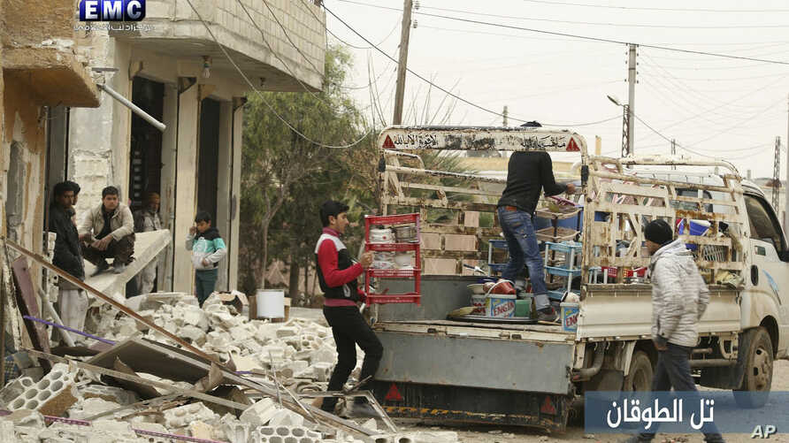 In this photo provided an. 4, 2018 by the Syrian anti-government activist group, Edlib Media Center, EMC, which has been authenticated based on its contents and other AP reporting, shows Syrian citizens load their belongings onto a pickup truck to fl