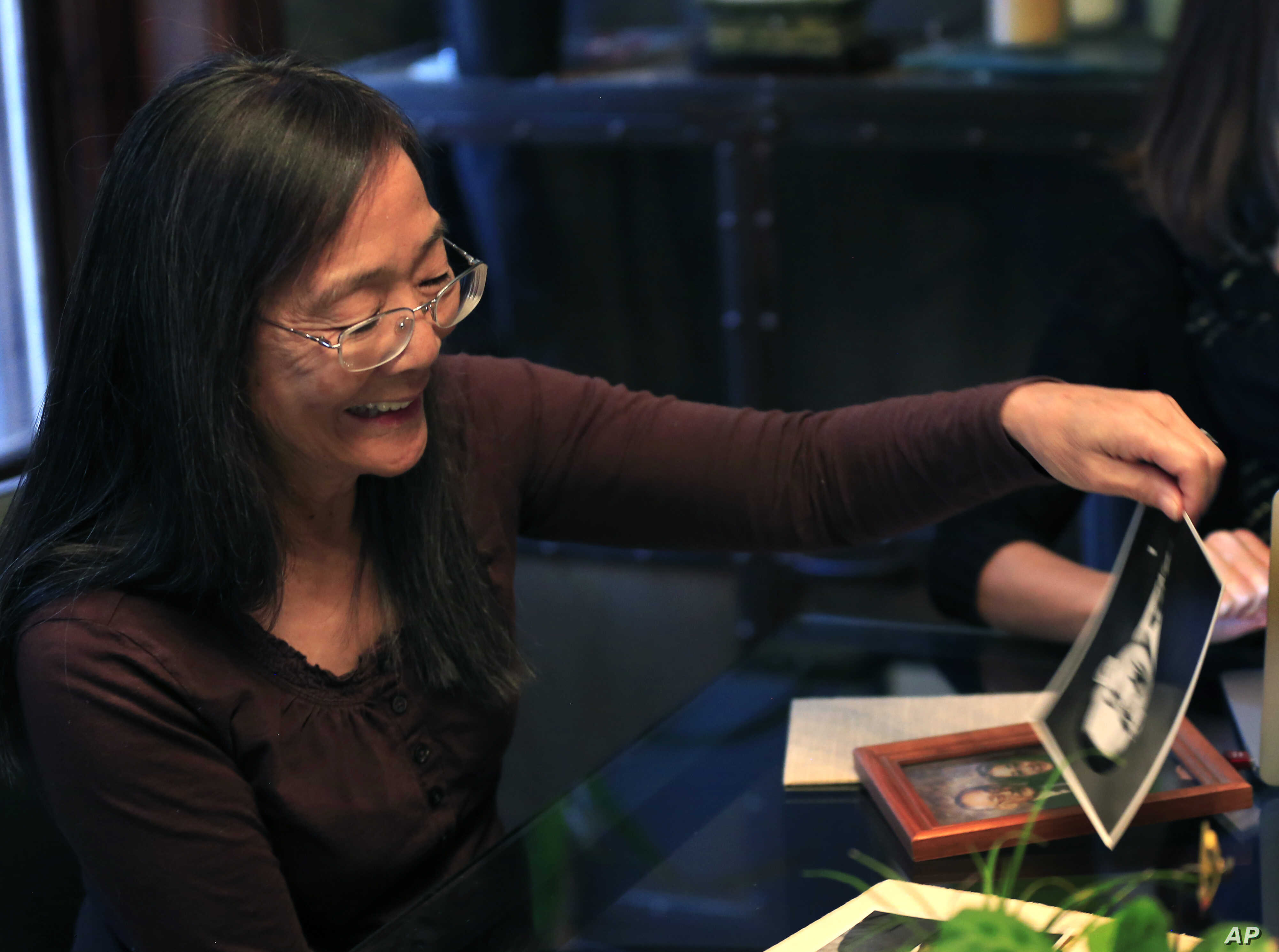 Laurie Yasui picks up photos of her father Minoru Yasui during an interview at her daughters home in Kansas City, Mo., Friday, Nov. 20, 2015.