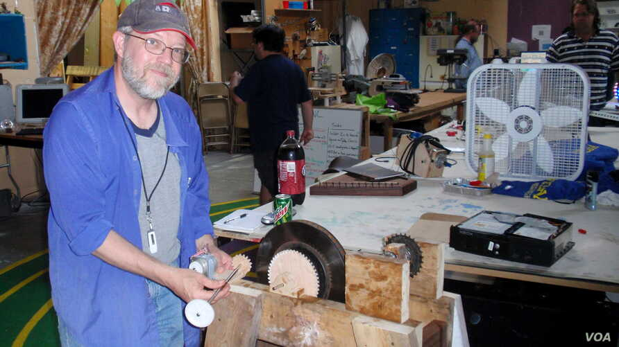 Michael Rohde demonstrates a pendulum-powered light that he's perfecting at OlyMEGA, the Olympia, Washington maker space. (Tom Banse for VOA)