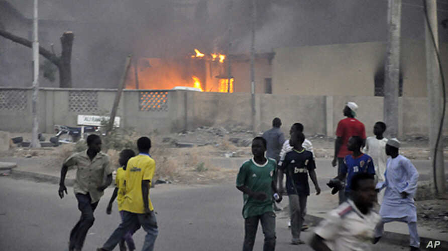 Smoke rises from the police headquarters as people run for safety in Nigeria's northern city of Kano, January 20, 2012.