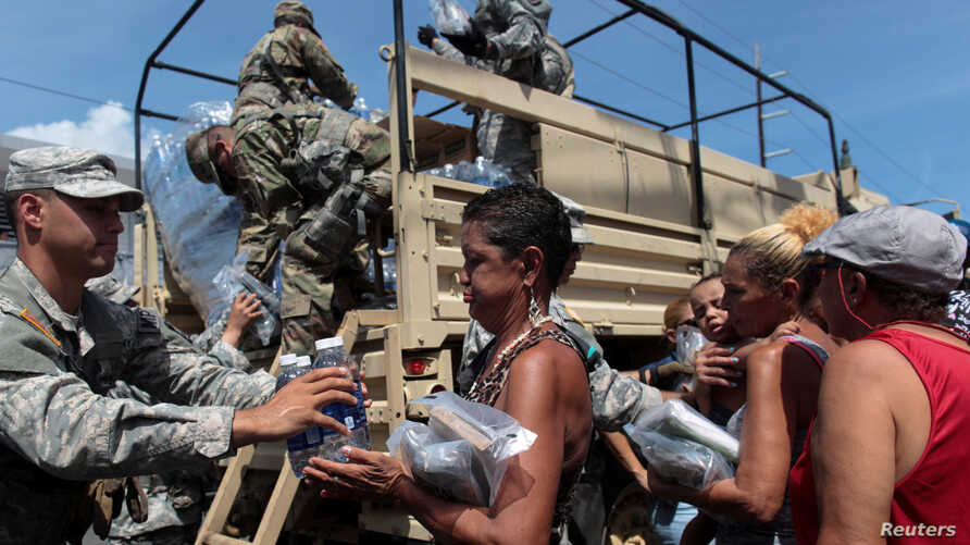 Soldiers of Puerto Rico's national guard distribute relief items to people, after the area was hit by Hurricane Maria in San Juan, Puerto Rico, Sept, 24, 2017.