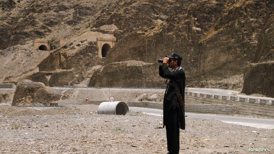A member of Pakistan's Frontier Corps uses binoculars to survery the border region outside Torkham, Pakistan, June 16, 2016.