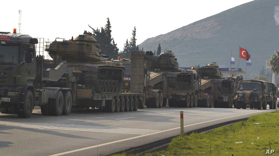 FILE - A convoy of Turkish military trucks carrying tanks and armoured personnel carriers destined for Syria in preparation for a possible military offensive, moves in Hatay province, southeastern Turkey, near the border with Syria, Jan. 14, 2019.