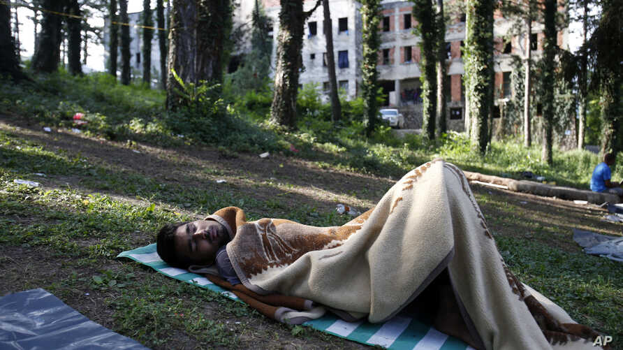 FILE - A migrant man sleeps on the ground at a makeshift migrant camp in Bihac, 450 kilometers northwest of Sarajevo, Bosnia, Aug. 14, 2018. Impoverished Bosnia must race against time to secure proper shelters for at least 4,000 migrants and refugees
