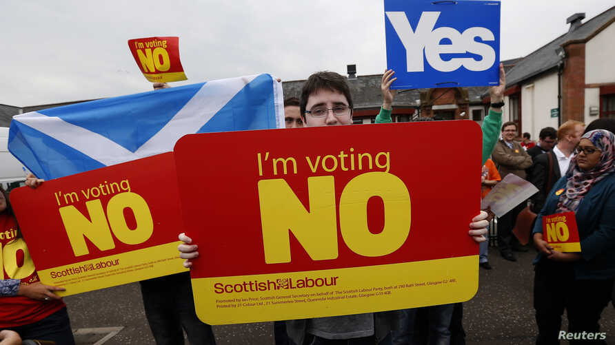 Opposing supporters wait for the leader of Britain's opposition Labour Party, Ed Miliband, during a campaign visit, ahead of the forthcoming Scottish vote for independence from the United Kingdom,  in East Kilbride, Scotland, Sept. 4, 2014.